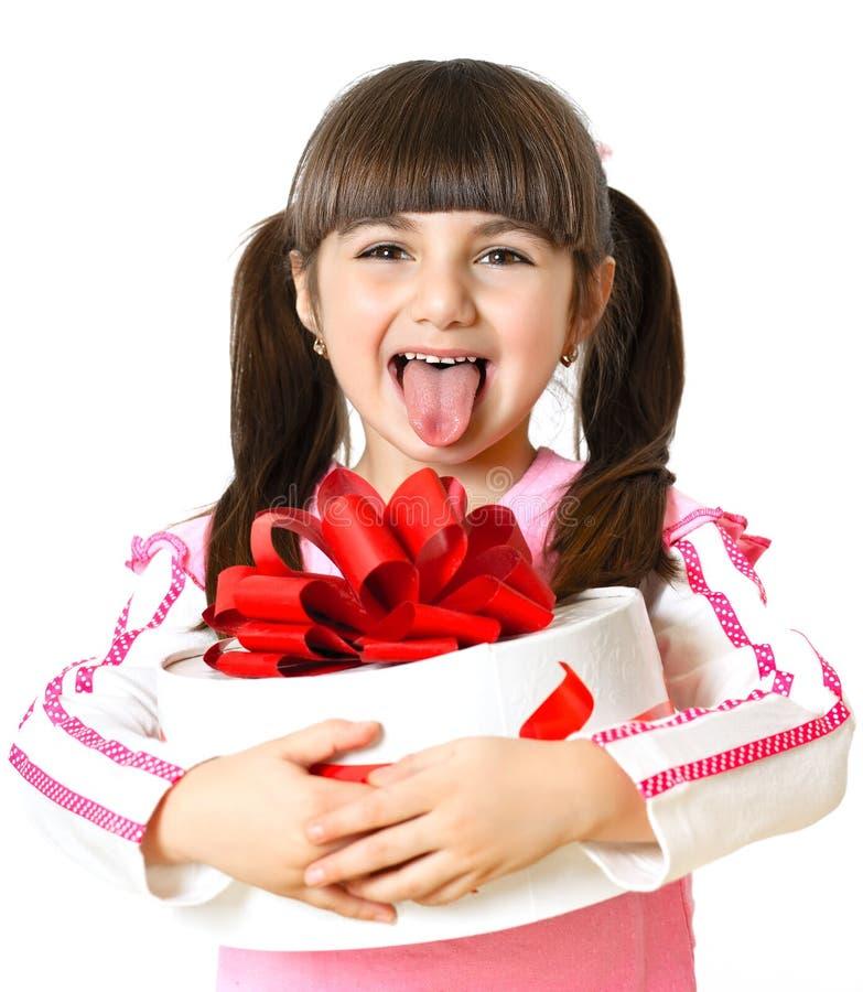 Kleines Mädchen mit einem Geschenk auf weißem Hintergrund stockfotografie