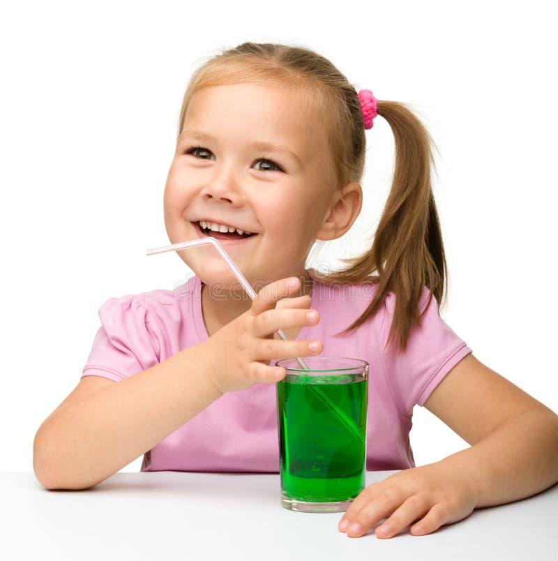 Kleines Mädchen mit einem Glas des Estragongetränks lizenzfreie stockfotografie