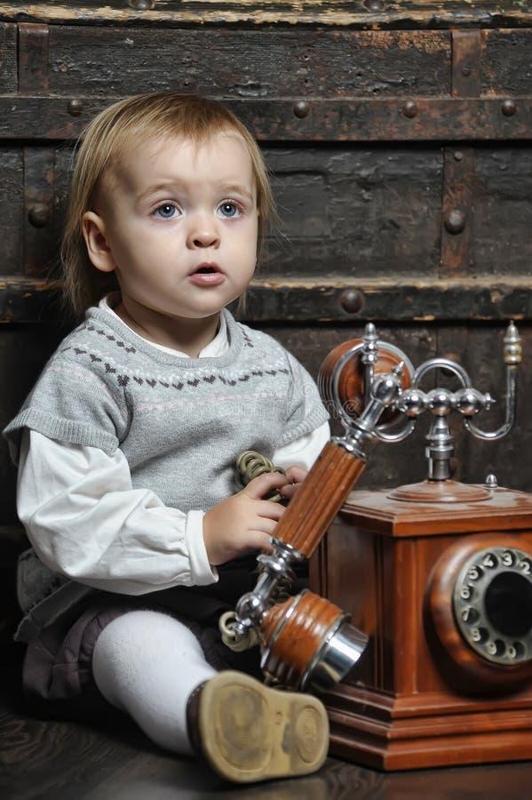 Kleines Mädchen mit einem Retro- Telefon stockfotografie