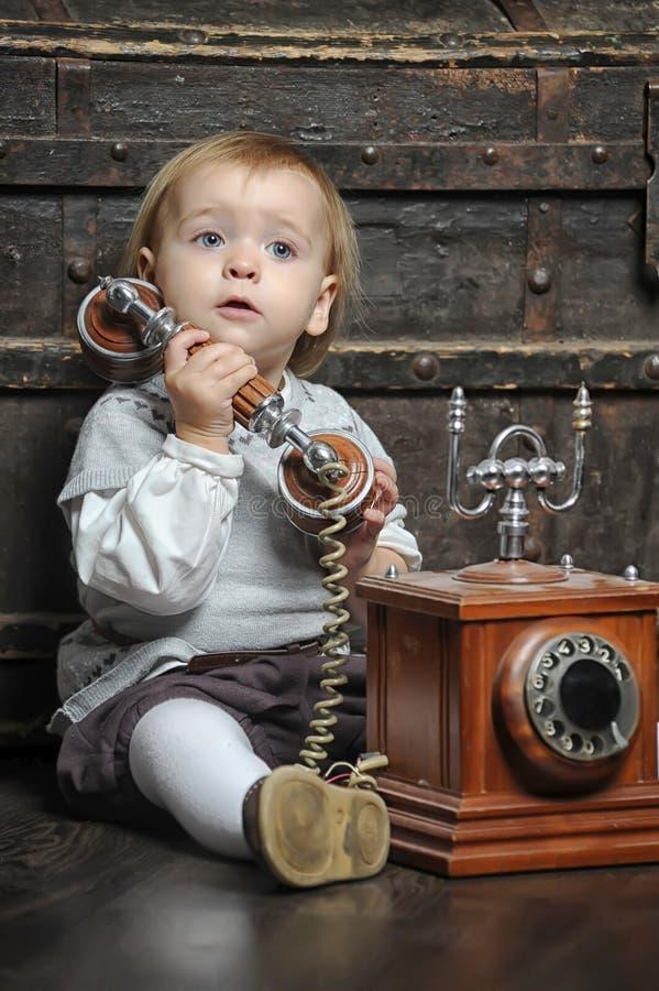 Kleines Mädchen mit einem Retro- Telefon lizenzfreies stockbild