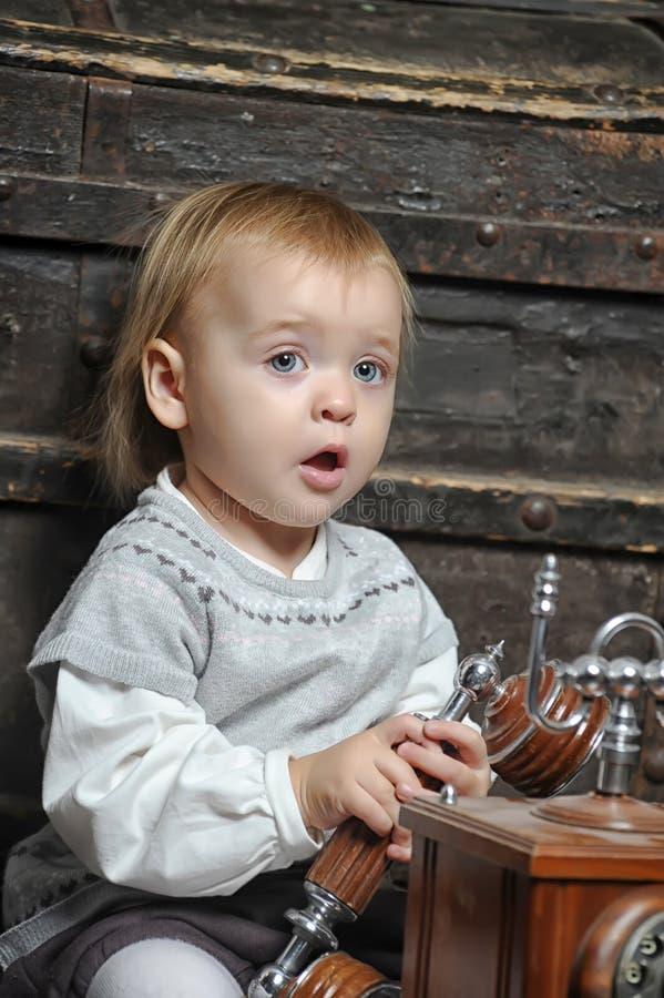 Kleines Mädchen mit einem Retro- Telefon stockbilder