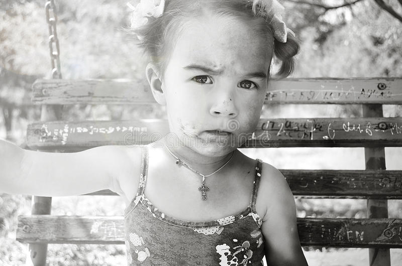 Kleines Mädchen mit einem schmutzigen Gesicht und Bögen auf einem Schwingen lizenzfreies stockbild