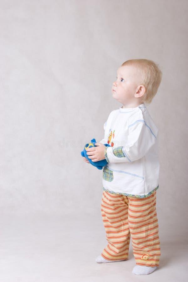 Kleines Mädchen mit einem Spielzeug schaut oben stockbilder