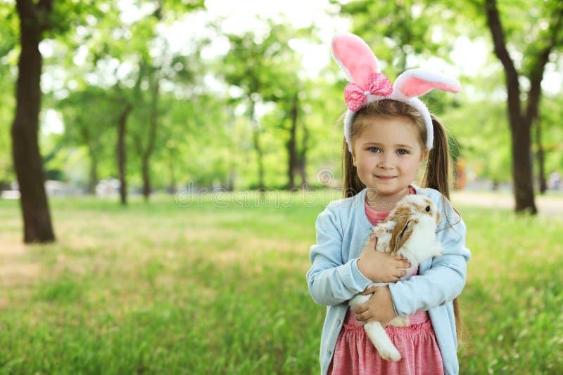 Kleines Mädchen mit entzückendem Häschen draußen stockfotos
