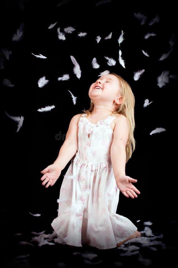 Kleines Mädchen mit fallenden weißen Federn lizenzfreie stockfotos