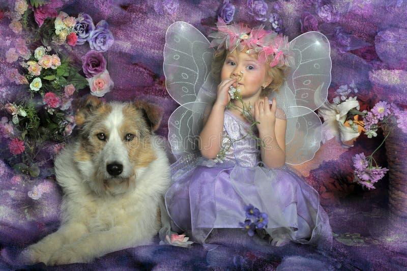 Kleines Mädchen mit Flügeln und einem Hund stockfotografie