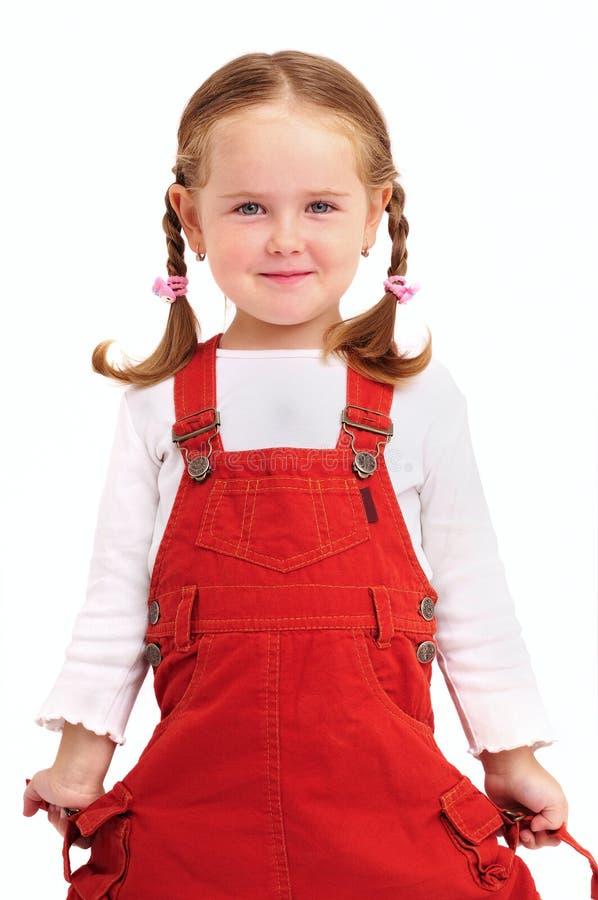 Kleines Mädchen mit Flechten und rotem Kleid lizenzfreies stockfoto