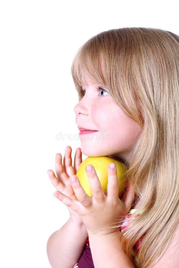 Kleines Mädchen mit gelbem Apfel lizenzfreie stockbilder