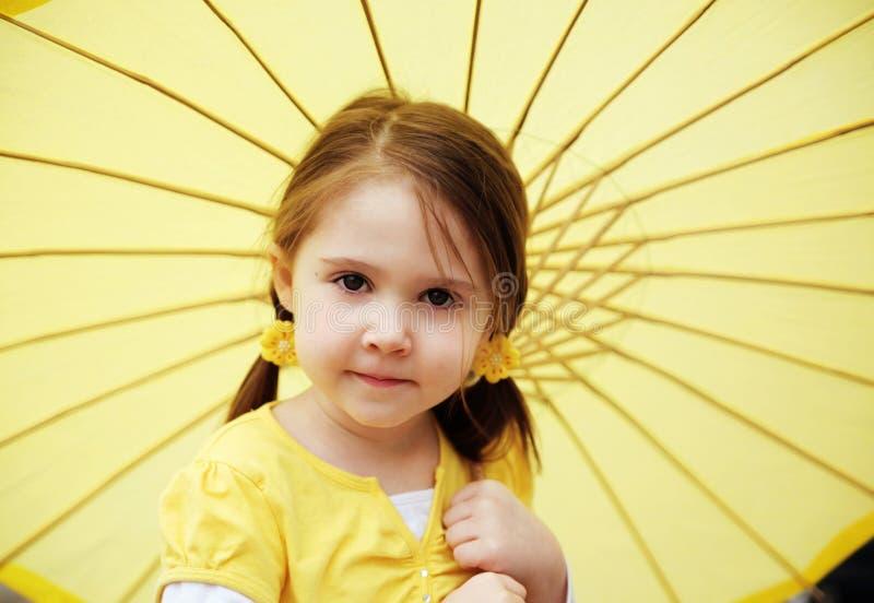 Kleines Mädchen mit gelbem Sonnenschirm stockfoto