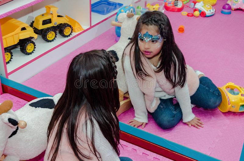 Kleines Mädchen mit gemaltem Gesicht schaut im Spiegel lizenzfreie stockbilder