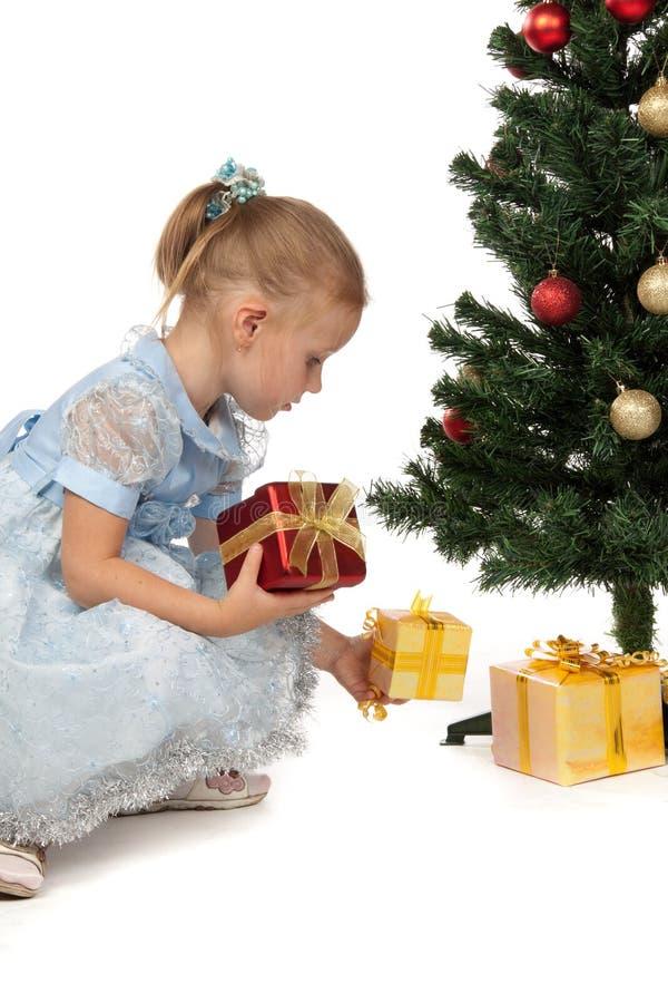 Kleines Mädchen mit Geschenken nähern sich einem Weihnachtsbaum lizenzfreies stockbild