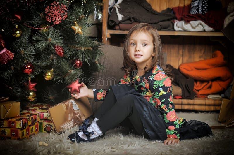 Kleines Mädchen mit Geschenken nähern sich einem Weihnachtsbaum stockbild