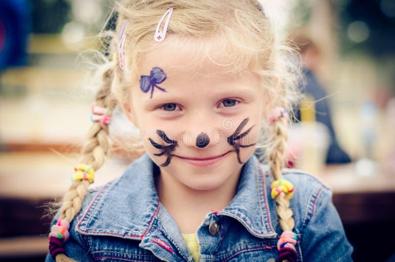 Kleines Mädchen mit Gesichtsanstrich stockfotos