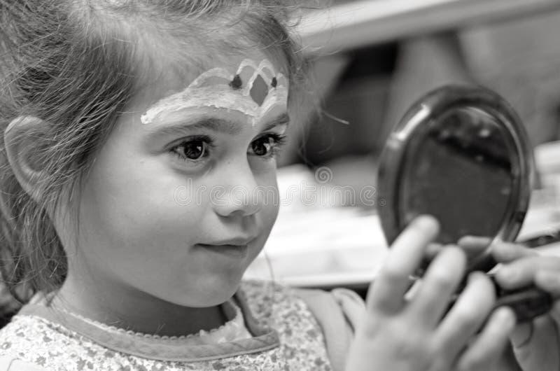 Kleines Mädchen mit Gesichtsmalerei betrachtet den Spiegel stockfotografie