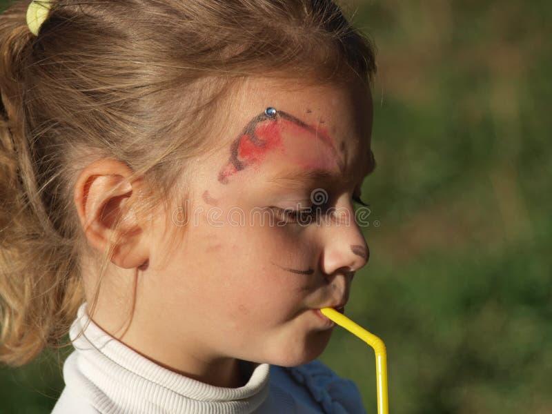 Kleines Mädchen mit Gesichtsmalerei trinkend durch ein Stroh stockfoto