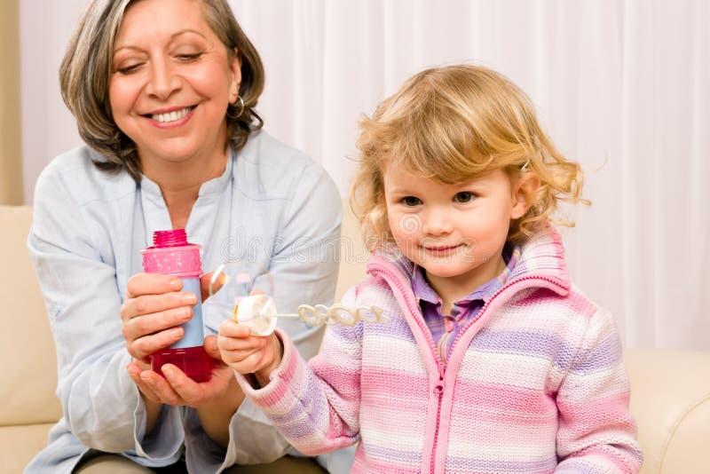 Kleines Mädchen mit Großmutterspiel-Luftblasengebläse stockfoto