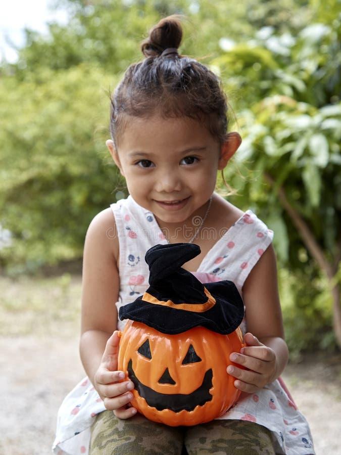 Kleines Mädchen mit Halloween-Kürbis lizenzfreies stockfoto
