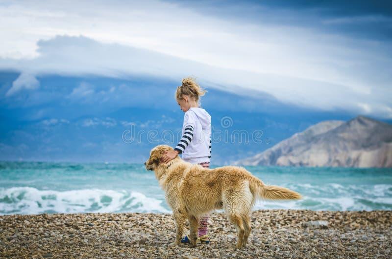 Kleines Mädchen mit Hund im felsigen Strand lizenzfreies stockbild