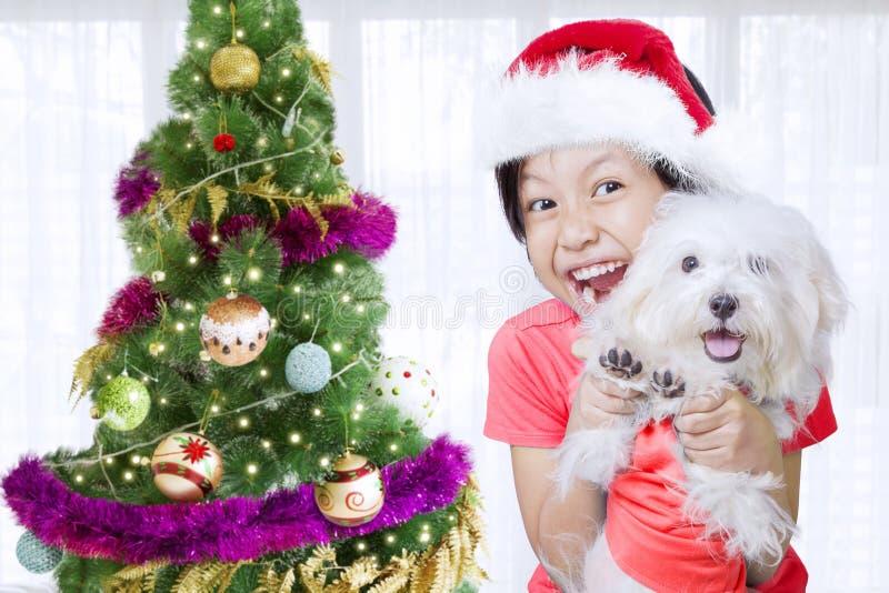 Kleines Mädchen mit ihrem Hund nahe Weihnachtsbaum stockbild