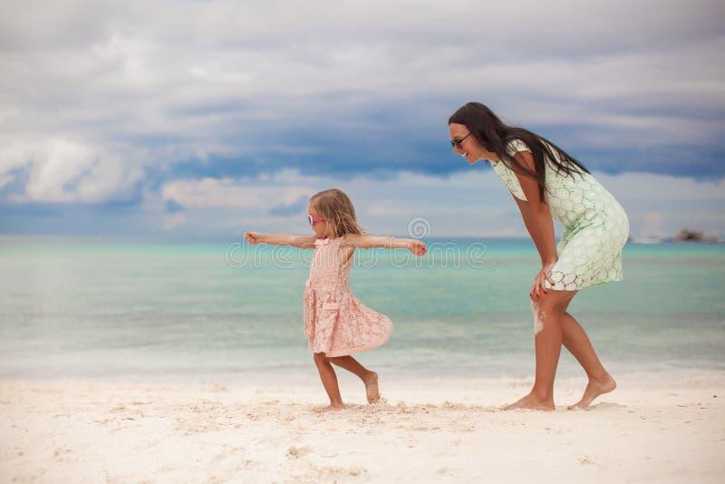 Kleines Mädchen mit ihrem Muttertanzen an weißem sandigem stockfoto
