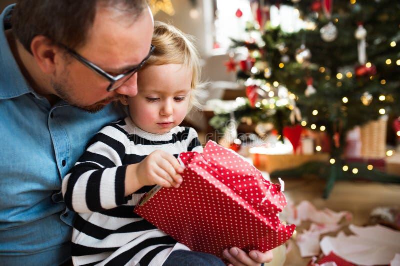 Kleines Mädchen mit ihrem Vateröffnung Weihnachtsgeschenk lizenzfreie stockfotografie