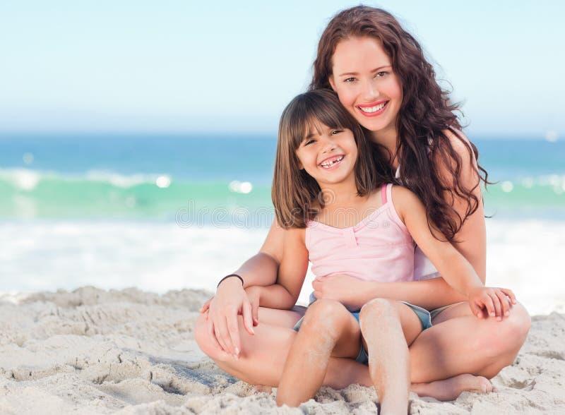 Kleines Mädchen mit ihrer Mutter am Strand lizenzfreies stockfoto
