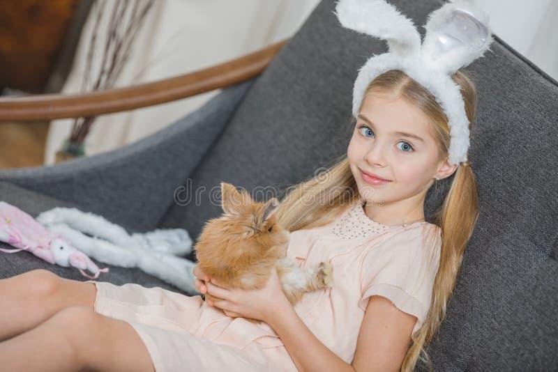 Kleines Mädchen mit Kaninchen stockbild