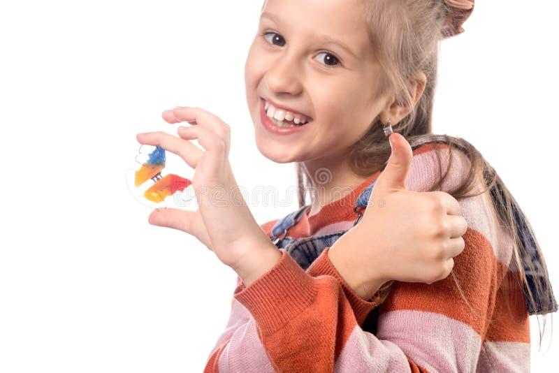 Kleines Mädchen mit Kieferorthopädie auf weißem Hintergrund isoliert stockfoto