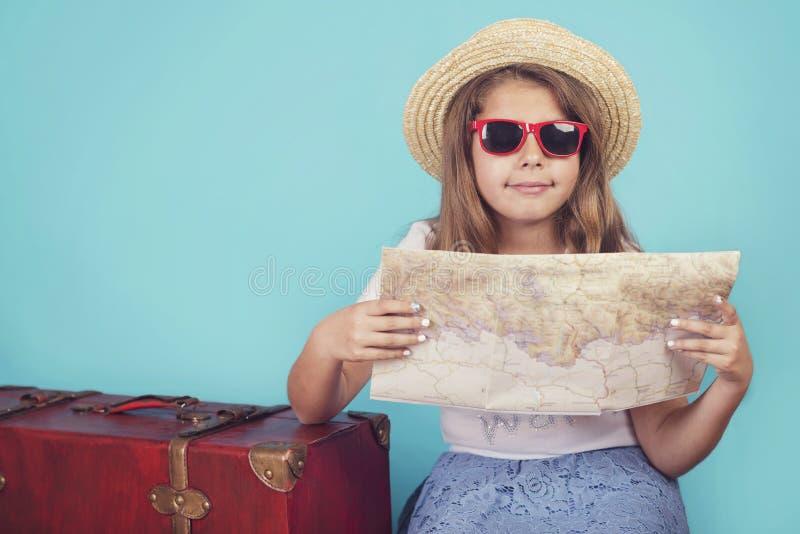 Kleines Mädchen mit Koffer und Karte lizenzfreie stockbilder