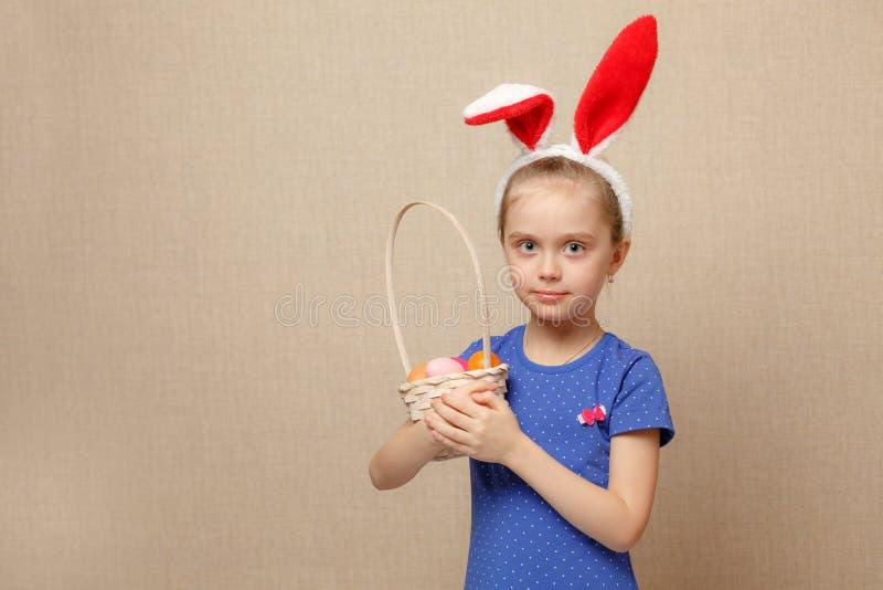 Kleines Mädchen mit Korb Ostereiern lizenzfreie stockfotos