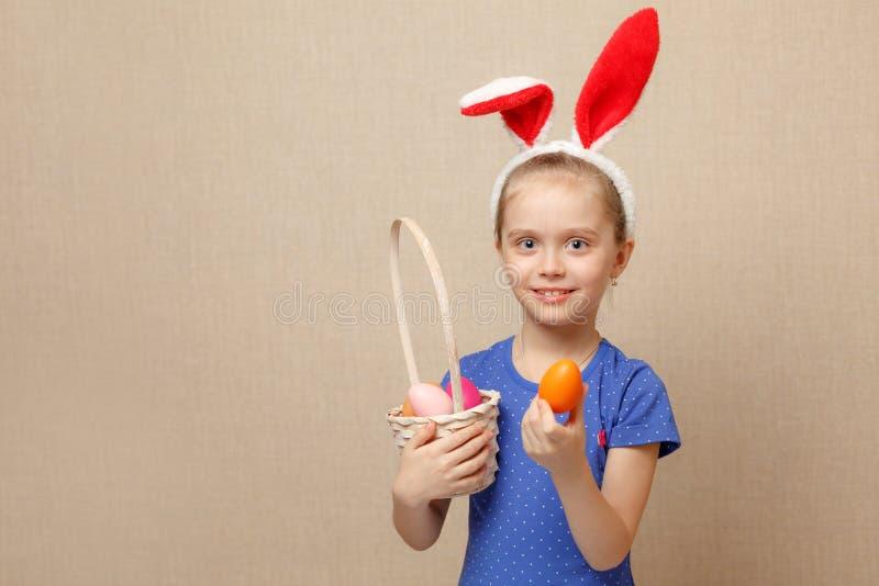 Kleines Mädchen mit Korb Ostereiern stockfotos