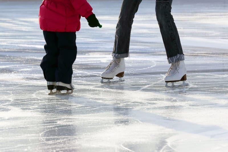 Kleines Mädchen mit Mutterrochen auf der Eisbahn lizenzfreie stockfotografie