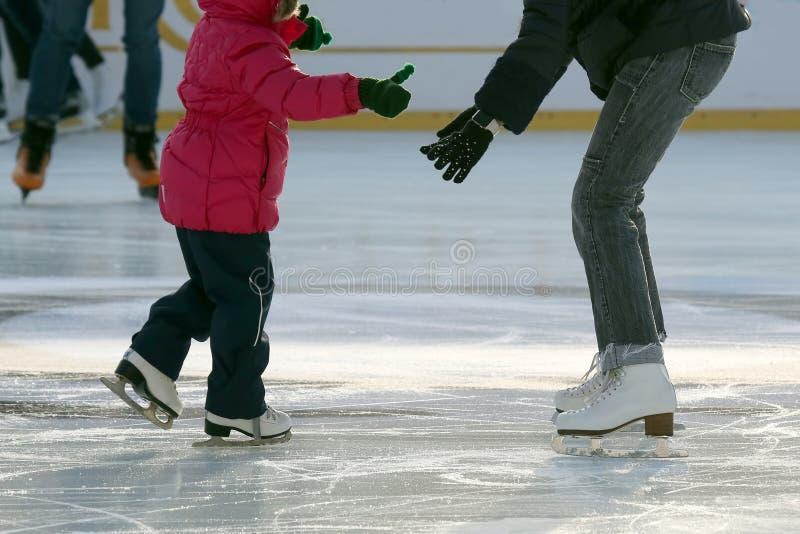 Kleines Mädchen mit Mutterrochen auf der Eisbahn stockbilder