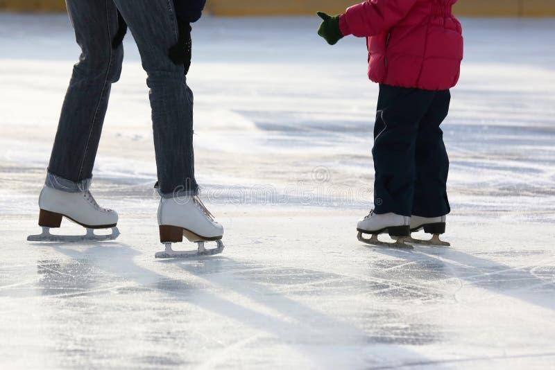 Kleines Mädchen mit Mutterrochen auf der Eisbahn stockfotografie
