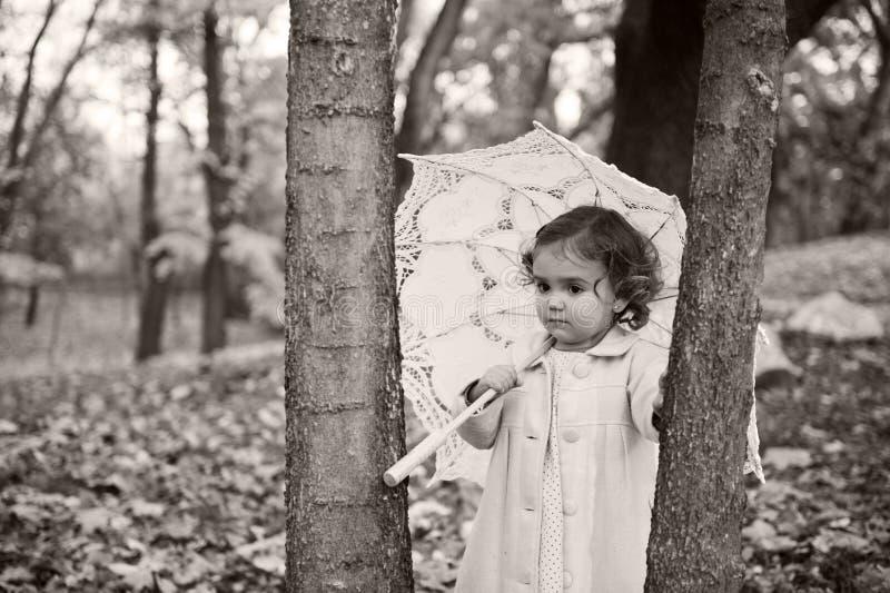 Kleines Mädchen mit Regenschirm stockbild