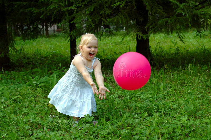 Kleines Mädchen mit rotem Ballon im Wald. lizenzfreie stockfotografie