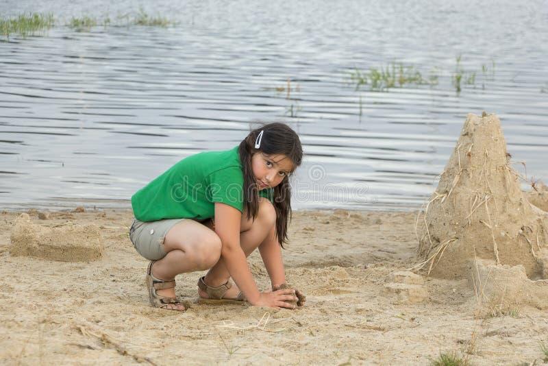 Kleines Mädchen mit Sandburg lizenzfreies stockfoto
