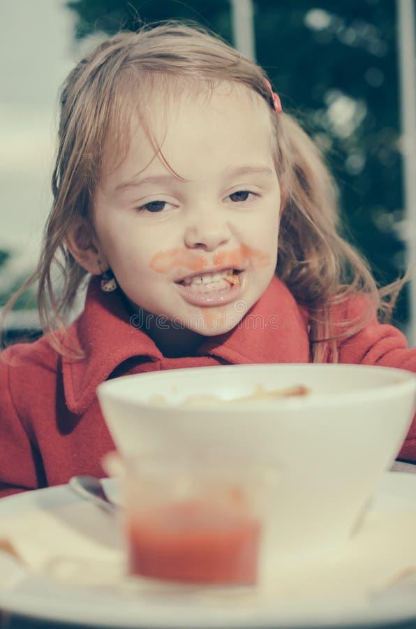 Kleines Mädchen mit schmutzigem Mund Fischrogen und Tomate essend stockfoto