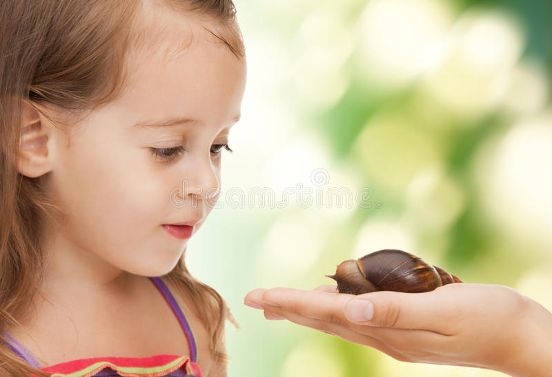 Kleines Mädchen mit Schnecke stockfotografie