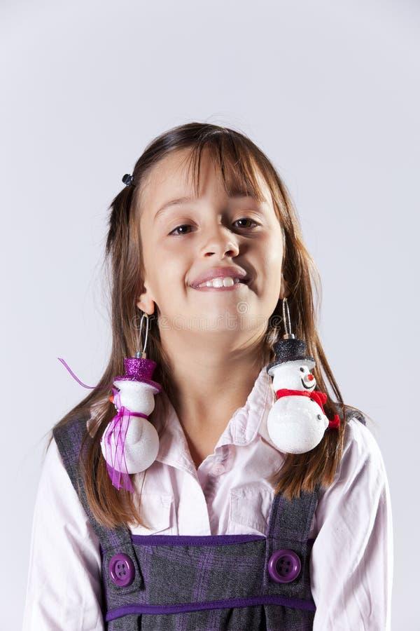 Kleines Mädchen mit Schneemanndekoration earings lizenzfreie stockbilder