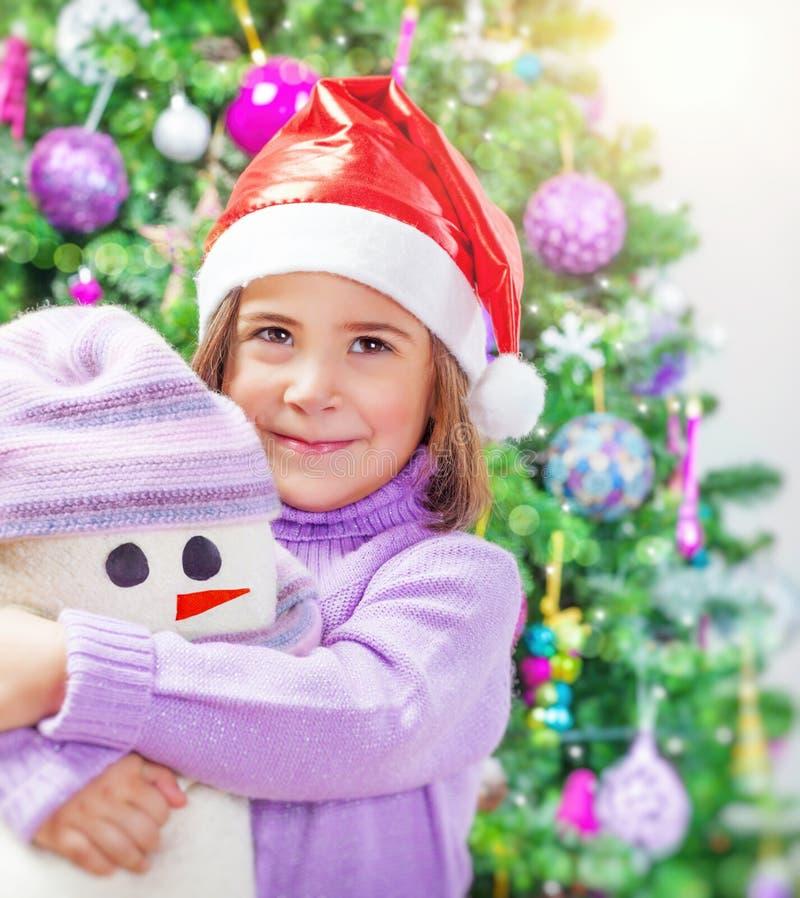 Kleines Mädchen mit Schneemannspielzeug stockfoto