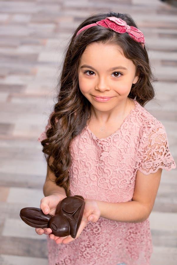 Kleines Mädchen mit Schokoladenhäschen lizenzfreies stockfoto