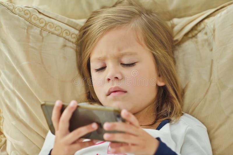 Kleines Mädchen mit smartphone lizenzfreie stockfotos