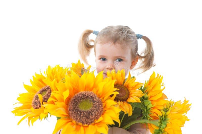 Kleines Mädchen mit Sonnenblumen lizenzfreies stockbild