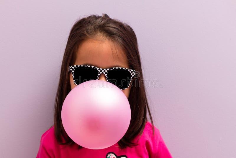 Kleines Mädchen mit Sonnenbrillen rosa Kaugummi explodierend lizenzfreies stockbild