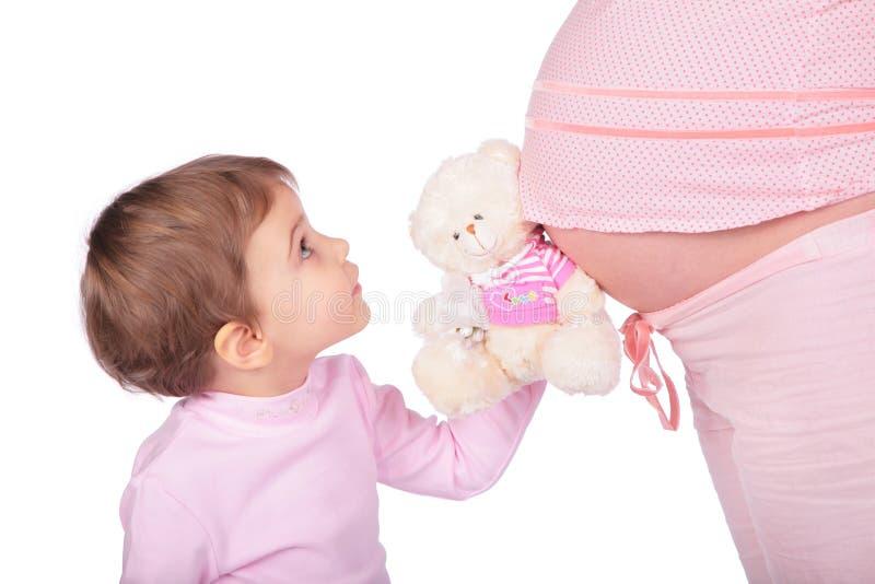 Kleines Mädchen mit Spielzeug und schwanger stockbild