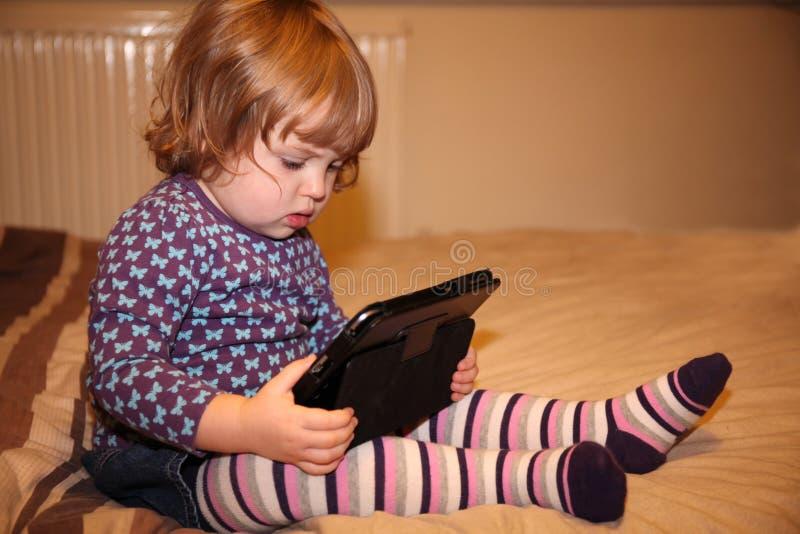 Kleines Mädchen mit Tablette stockbilder