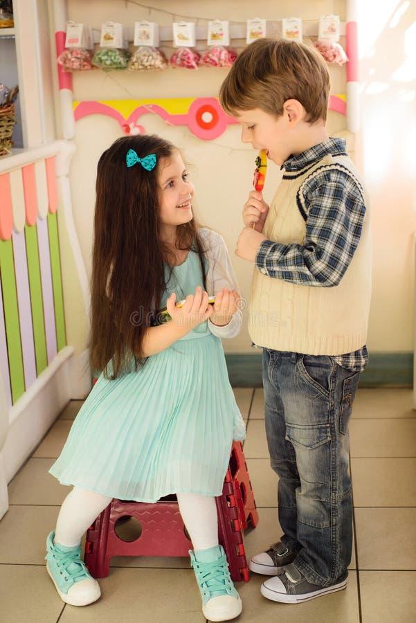 Kleines Mädchen mit Tablette lächelnd zum Jungen lizenzfreies stockbild