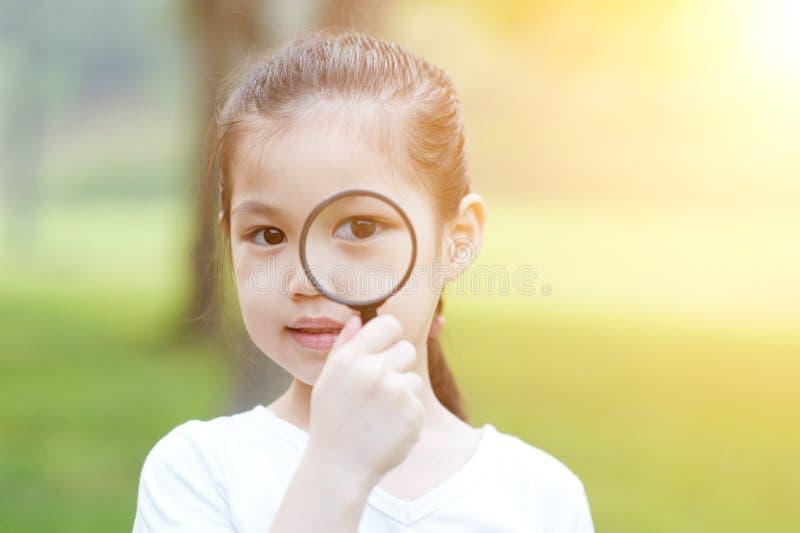 Kleines Mädchen mit Vergrößerungsglasglas an draußen stockfoto