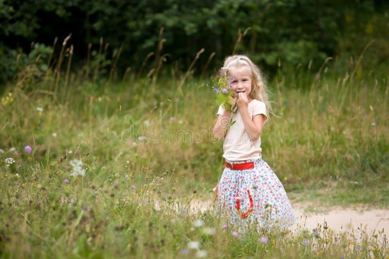 Kleines Mädchen mit wilden Blumen stockbild
